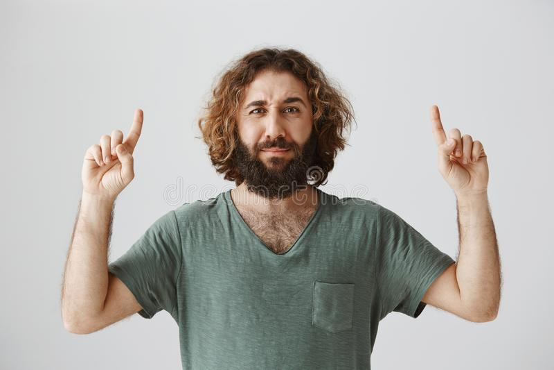 O indivíduo não é certo que gosta do que vê Retrato do arabian atrativo com cabelo encaracolado longo e da barba que apontam acim foto de stock