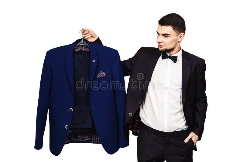 O indivíduo não conhece o que vestir o homem farpado novo guarda o terno no gancho foto de stock