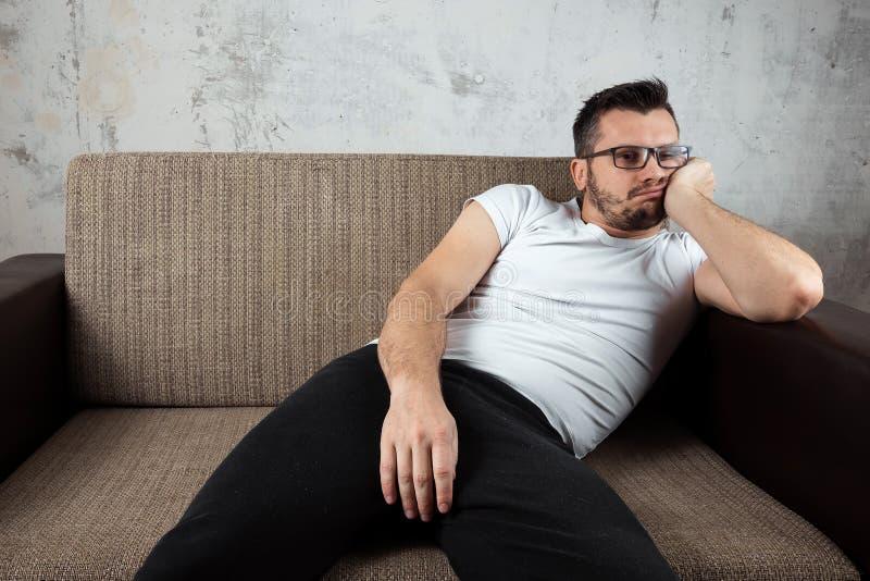 O indivíduo na camisa branca está encontrando-se no sofá O conceito da preguiça, apatia, frustração, procrastinação fotografia de stock