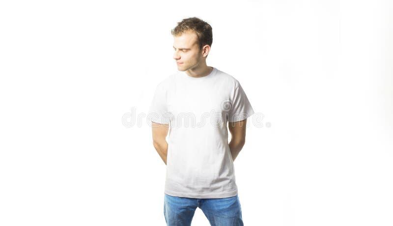 O indivíduo no t-shirt branco vazio, sorrindo em um fundo branco, zombaria acima, espaço livre, logotipo, projeto, molde para o p fotografia de stock