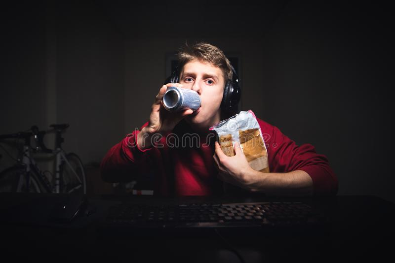 O indivíduo nos fones de ouvido guarda petiscos em seus mão e olhares no monitor do computador foto de stock royalty free