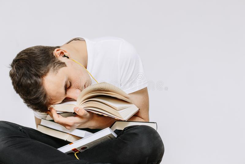 O indivíduo novo caiu livros de leitura adormecidos Fundo branco isolado fotos de stock