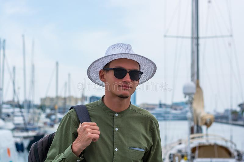 O indivíduo novo em um chapéu e nos óculos de sol está no porto de Barce fotos de stock royalty free