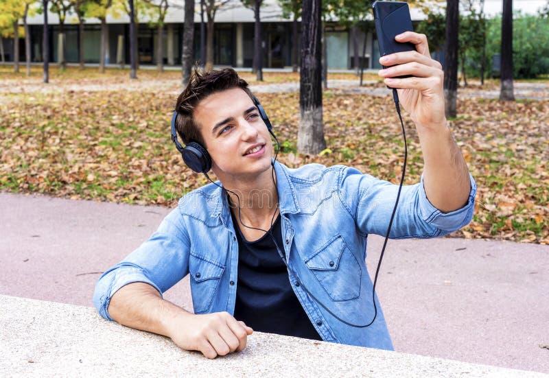 O indivíduo novo está fazendo o selfie em uma câmera Está vestindo o tre ocasional fotos de stock