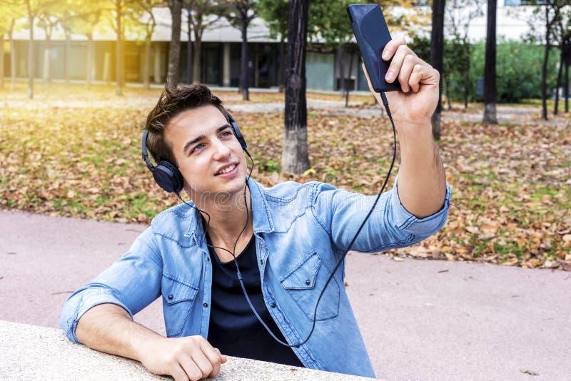 O indivíduo novo está fazendo o selfie em uma câmera Está vestindo o tre ocasional fotos de stock royalty free