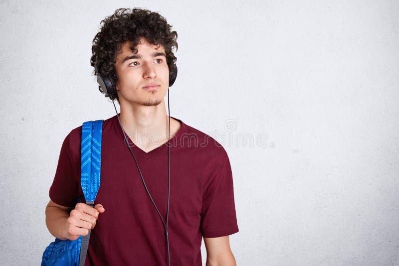 O indivíduo novo pensativo com os fones de ouvido na cabeça e na mochila azul, camisa ocasional marrom vestindo de t, escuta a mú foto de stock royalty free