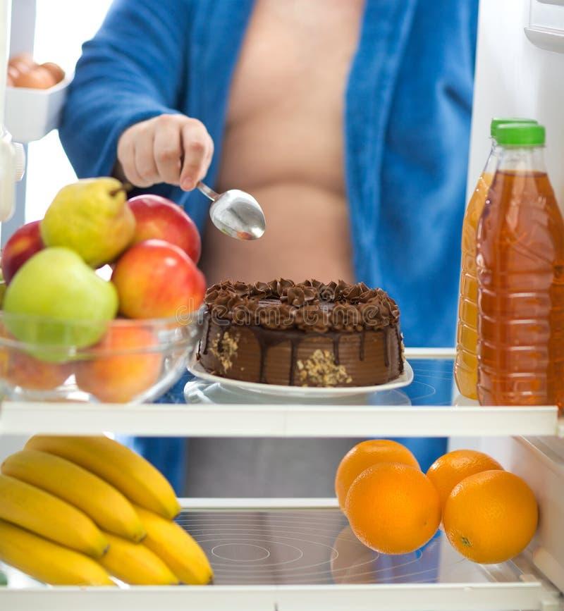 O indivíduo obeso prefere o bolo de chocolate do refrigerador do que o fruto fotos de stock