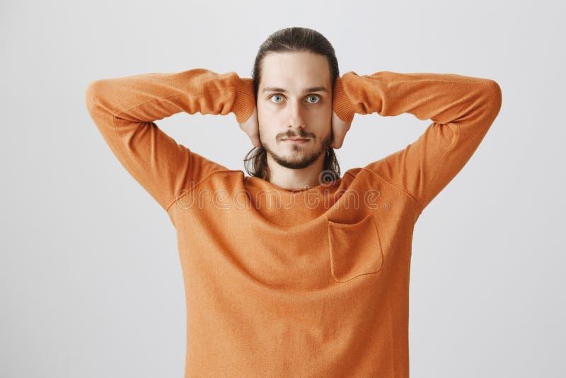 O indivíduo protege suas orelhas das mentiras e das promessas vazias Retrato do modelo masculino europeu sério com a barba na cam fotografia de stock royalty free