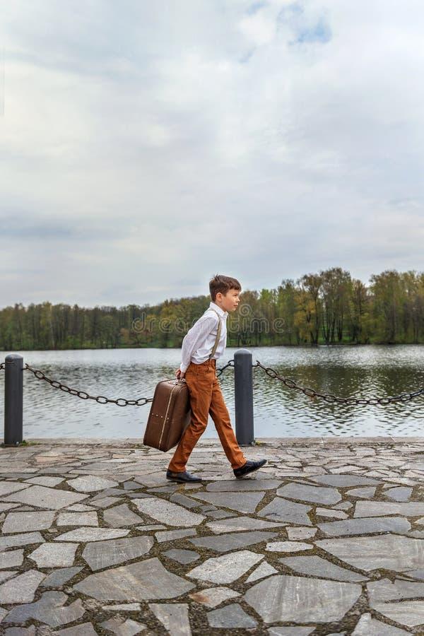 o indivíduo rústico na roupa antiquado passeia no cais com uma mala de viagem velha retro enorme imagens de stock royalty free