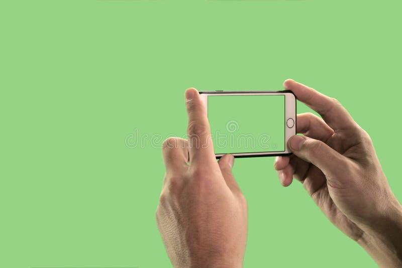 O indivíduo toma imagens ou dispara no vídeo em um telefone celular Close-up das mãos de um homem com um dispositivo em um fundo  fotos de stock