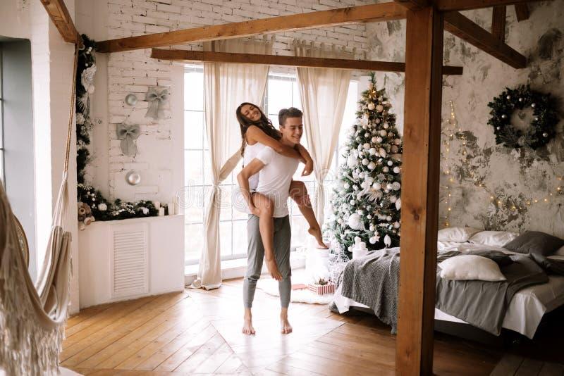 O indivíduo vestido no t-shirt e no short brancos mantém a menina no seu para trás em uma sala decorada acolhedor com feixes de m fotografia de stock