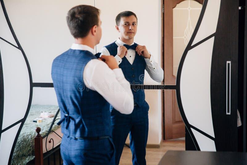 O indivíduo vestiu seu terno de negócio e amarrou um laço à moda O homem recolhe na frente do espelho e sorri no seu imagens de stock royalty free