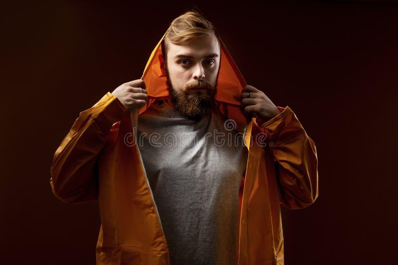 O indiv?duo com uma barba e um bigode vestidos em um t-shirt cinzento e em um revestimento amarelo com uma capa est? estando em u foto de stock royalty free