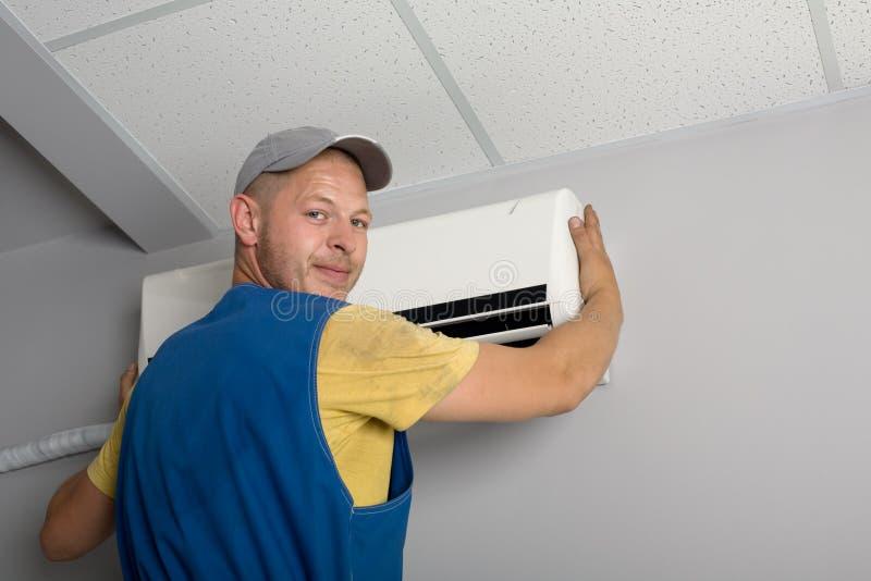O instalador ajusta um condicionador de ar novo imagem de stock