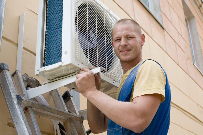 O instalador ajusta um condicionador de ar novo fotos de stock
