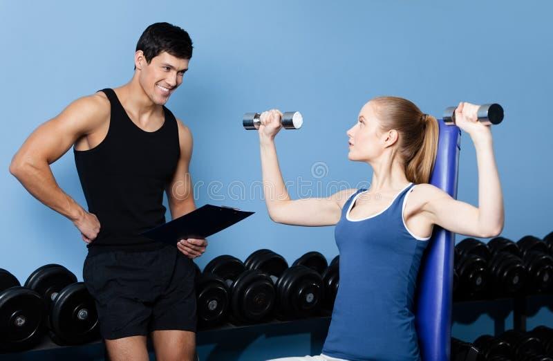 O instrutor controla ações dos esportes da mulher bonita foto de stock royalty free
