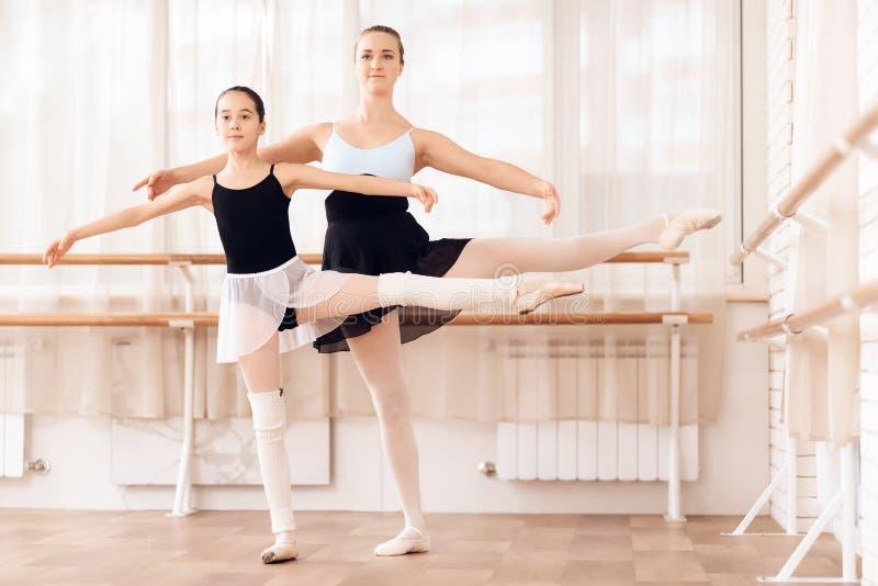 O instrutor da bailarina nova das ajudas da escola do bailado executa exercícios coreográficos diferentes fotos de stock