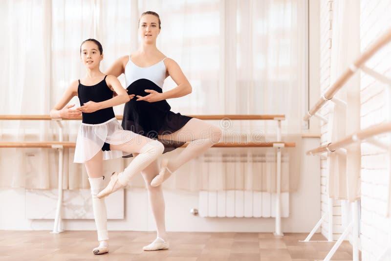 O instrutor da bailarina nova das ajudas da escola do bailado executa exercícios coreográficos diferentes imagem de stock