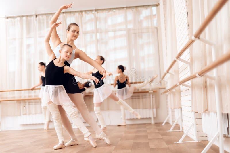 O instrutor da bailarina nova das ajudas da escola do bailado executa exercícios coreográficos diferentes imagens de stock royalty free