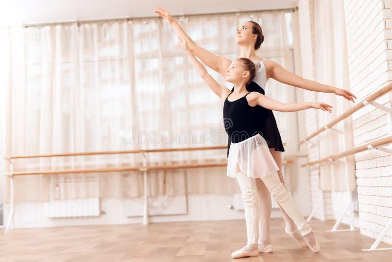 O instrutor da bailarina nova das ajudas da escola do bailado executa exercícios coreográficos diferentes foto de stock