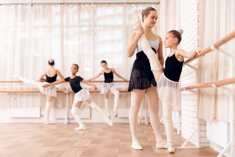 O instrutor da bailarina nova das ajudas da escola do bailado executa exercícios coreográficos diferentes imagem de stock royalty free