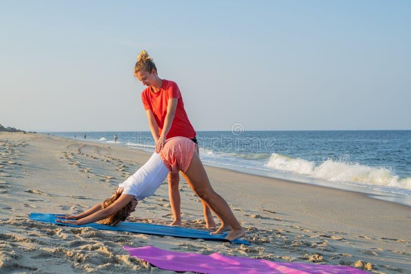 O instrutor da classe da ioga ajuda o novato a fazer exerc?cios do asana Mulher que faz para baixo - enfrentar o exercício do cão imagem de stock