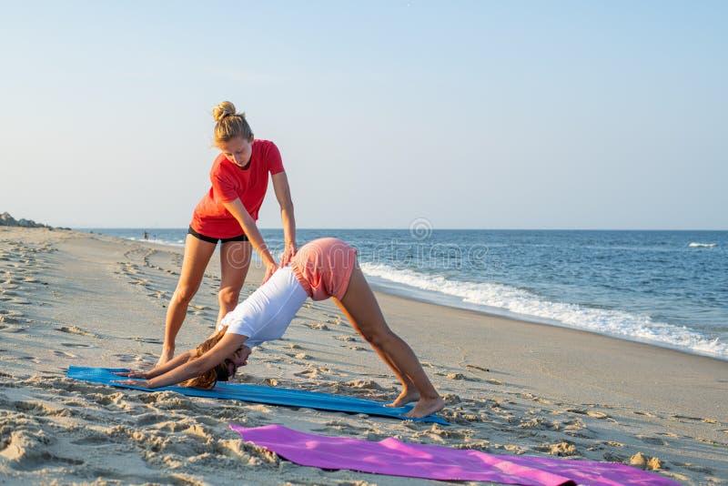 O instrutor da classe da ioga ajuda o novato a fazer exerc?cios do asana Mulher que faz para baixo - enfrentar o exercício do cão imagem de stock royalty free