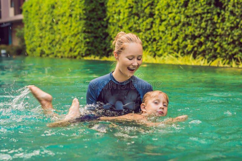 O instrutor da natação da mulher para crianças está ensinando um menino feliz nadar na associação imagem de stock