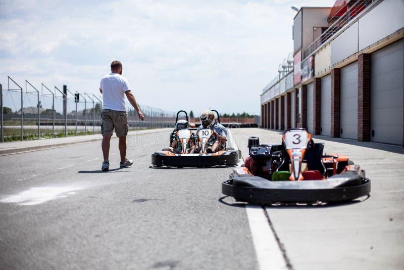 O instrutor da trilha do kart conduz a instrução antes da raça Emparelhe karting Pai e filho no verão ativo foto de stock royalty free