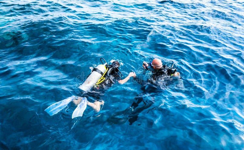 O instrutor de mergulho que guarda discípulo entrega na água azul imagem de stock royalty free