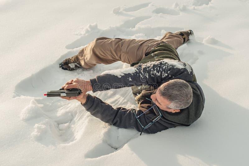 O instrutor demonstra a posição do corpo do tiro da arma sobre a escala de tiro imagens de stock
