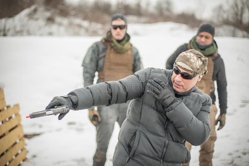 O instrutor demonstra o tiro t?tico da arma do combate da a??o a seus estudantes foto de stock