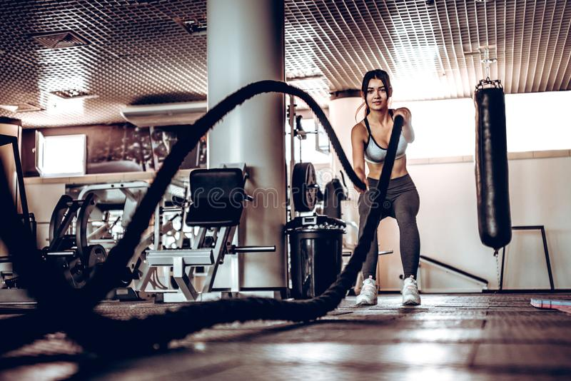 O instrutor muscular atrativo poderoso da mulher faz o exercício da batalha com cordas no gym fotografia de stock royalty free