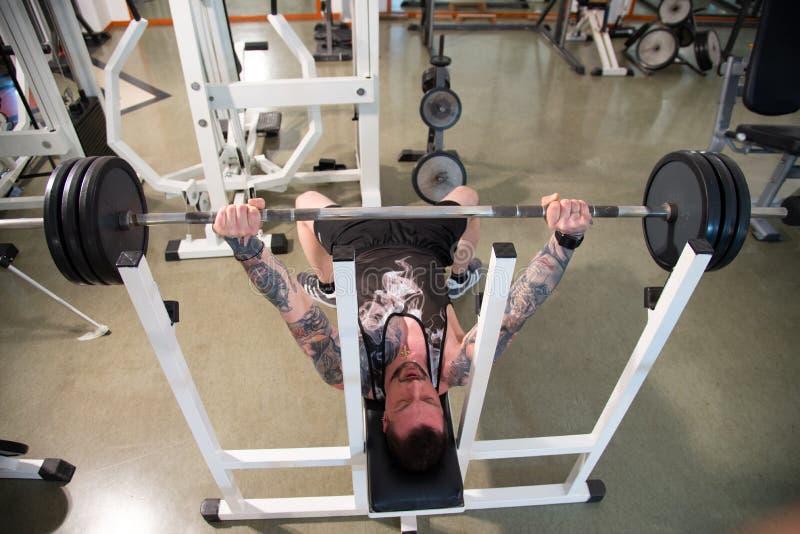 O instrutor pessoal com um corpo tattooed faz o exercício no gym usando um banco liso com apoio do barbell fotos de stock