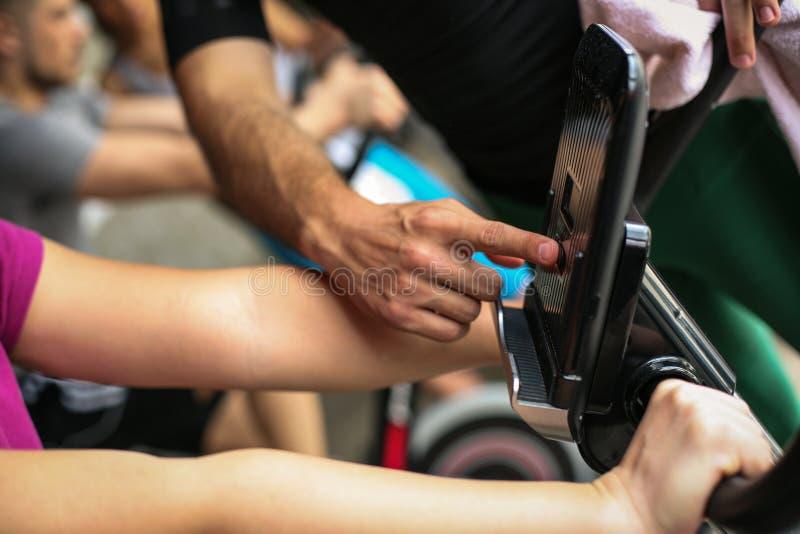O instrutor pessoal muda a velocidade da bicicleta fotos de stock