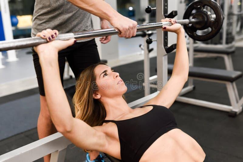 O instrutor pessoal que ajuda uma jovem mulher levanta peso imagem de stock