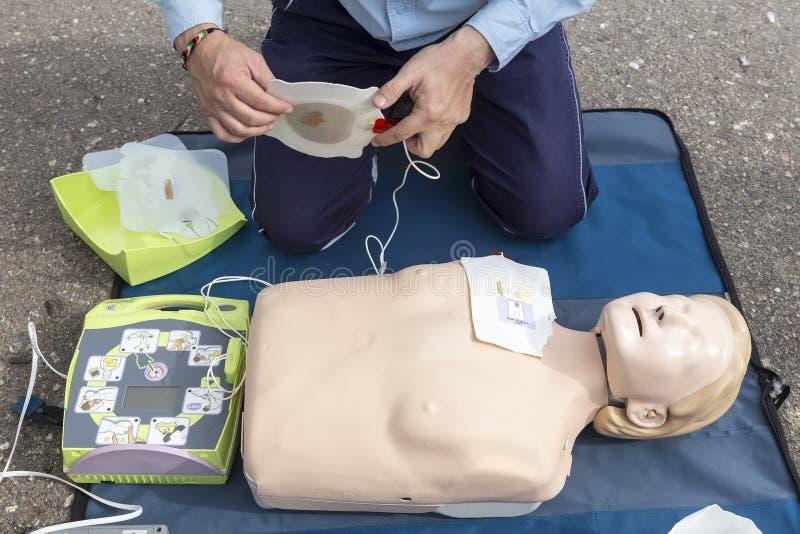 O instrutor que mostra o CPR na boneca do treinamento Livre primeiros socorros foto de stock