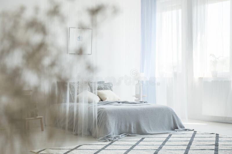 O interior branco do quarto com tapete, janela com drapeja e rei imagem de stock