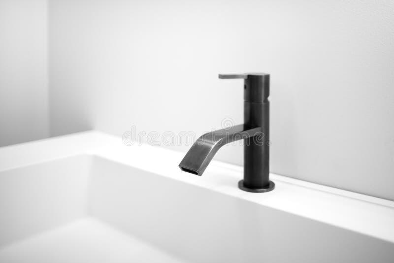 O interior cinzento branco do banheiro com dissipador branco e o techno moderno preto do close-up denominam o torneira fotografia de stock royalty free