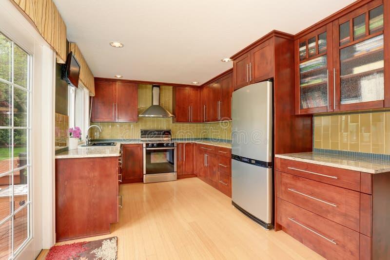 O interior da sala da cozinha com os armários e luz marrons modernos tonifica o assoalho de folhosa fotografia de stock