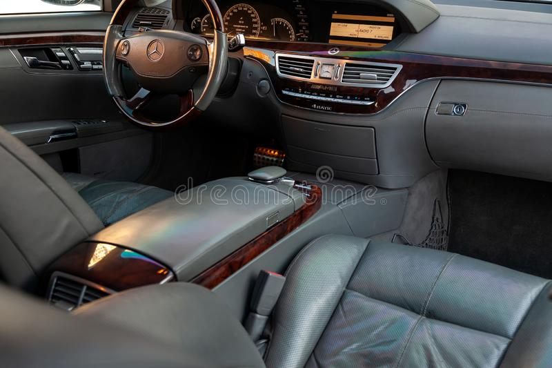 O interior de um carro caro da classe executiva dentro dos assentos dianteiros do couro perfurado genuíno, o painel de controle c fotografia de stock royalty free