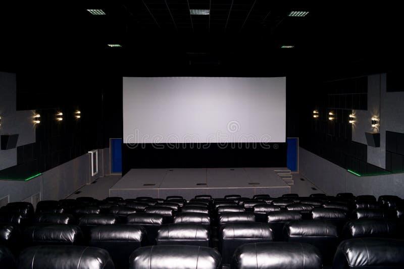 O interior de um salão do cinema com assentos de couro pretos e uma tela branca O filme não mostra e nenhuns povos imagens de stock royalty free