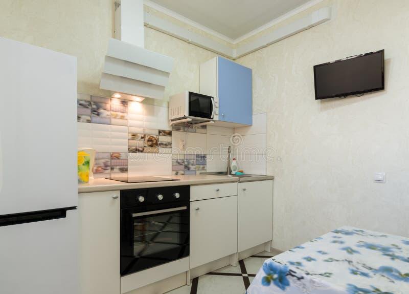 O interior de uma cozinha pequena com uma tevê na parede fotos de stock