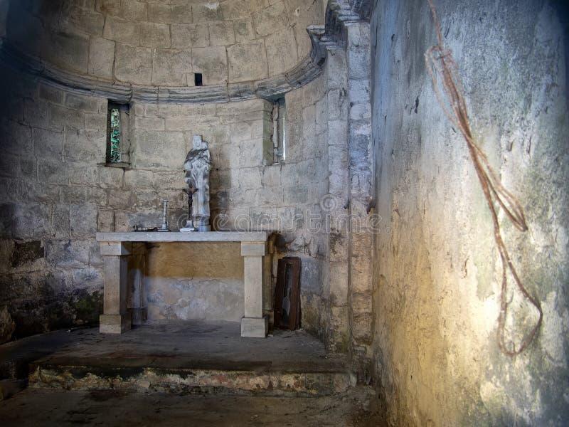 O interior de uma igreja antiga, pequena e esquecida Lunigiana, Itália Com estátua e crucifixo imagem de stock
