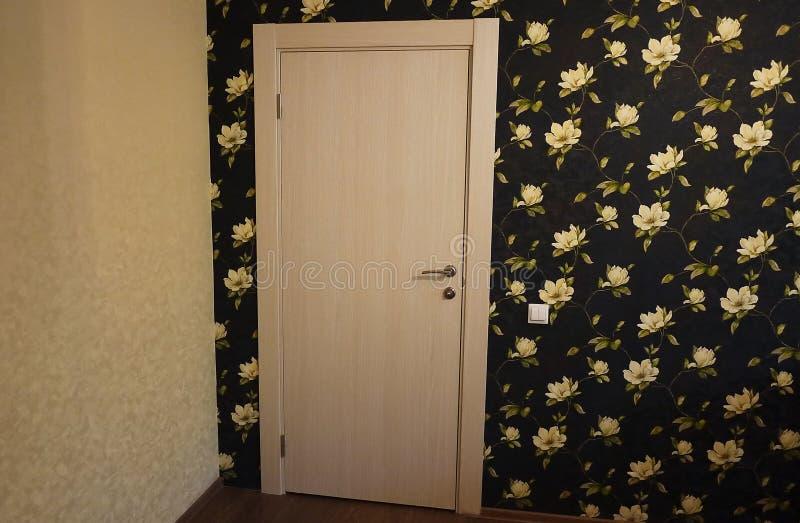 O interior de uma sala instalada com um interior novo Porta A porta instalada complementa harmoniosamente o interior da sala, b imagem de stock