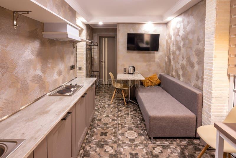 O interior de uma sala de visitas pequena na sala de hotel, combinado com a cozinha imagens de stock royalty free