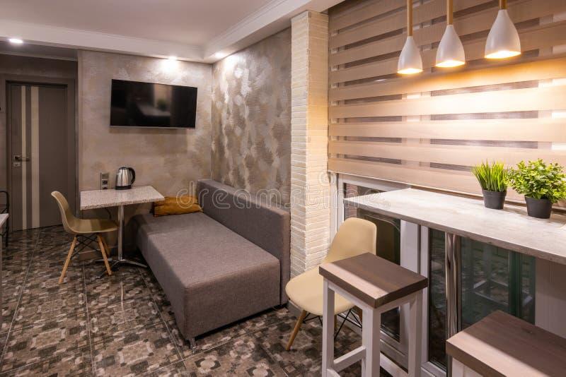 O interior de uma sala de visitas pequena na sala de hotel, combinado com a cozinha imagem de stock