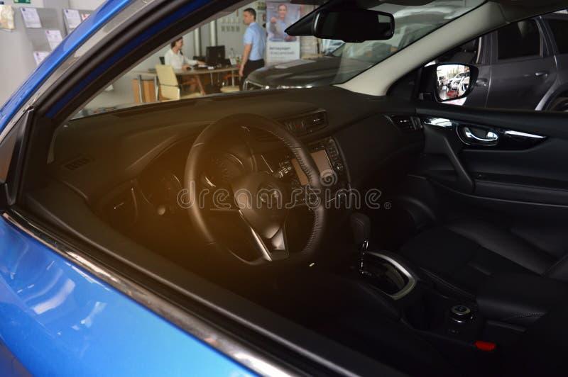 O interior do carro, no fundo um homem compra um carro e redige documentos Compra do carro do concessionário automóvel, empréstim fotografia de stock