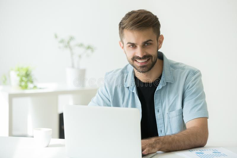 O interno ou o diretor de marketing feliz que usam o computador que olha vieram fotografia de stock