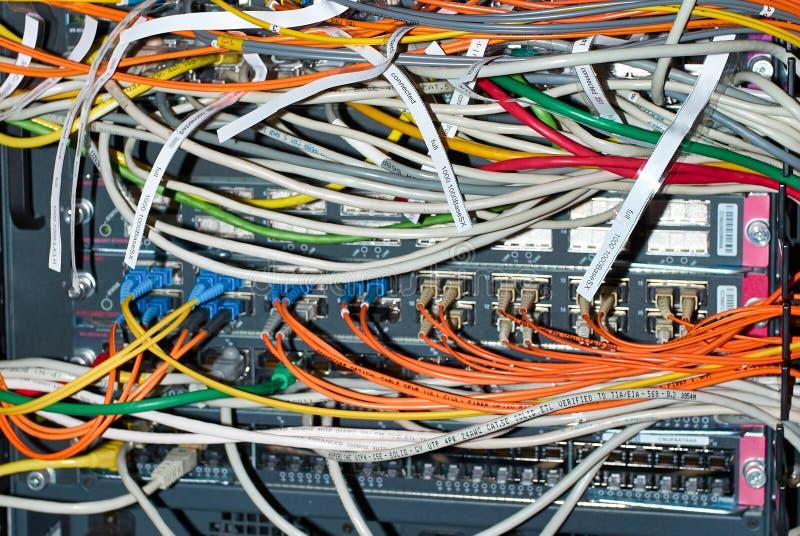 O interruptor de rede com ótico e ethernet conectou fios imagem de stock royalty free